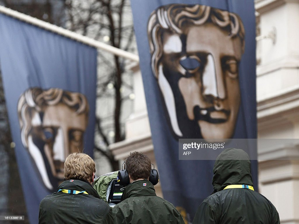 Cameramen stand by their equipment as preparations are made on the red carpet for the BAFTA British Academy Film Awards outside the Royal Opera House in London on February 10, 2013.
