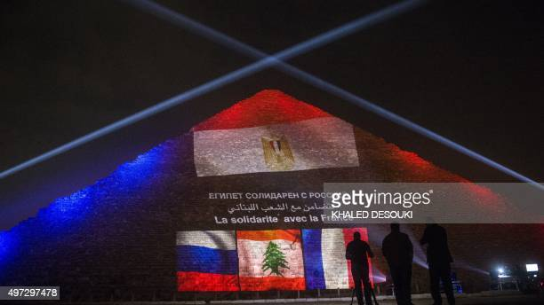 Cameramen stand in front of the great pyramid of Khufu illuminated with the French Lebanese and Russian flags in Giza outskirt of Cairo on November...