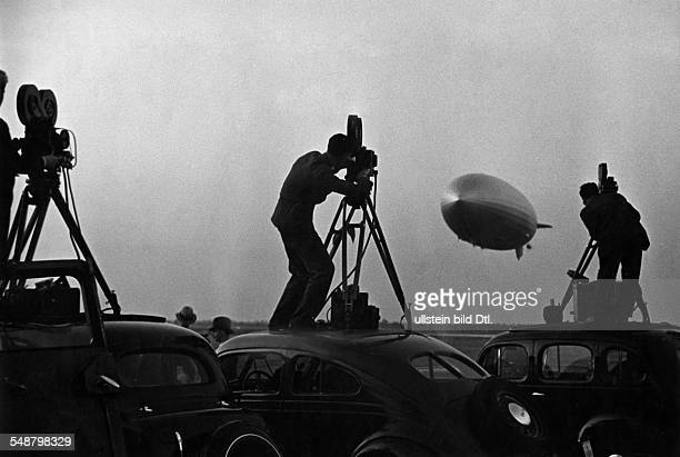 Cameramen standing on cars filming the return of the LZ 129 Hindenburg from its North Atlantic flight
