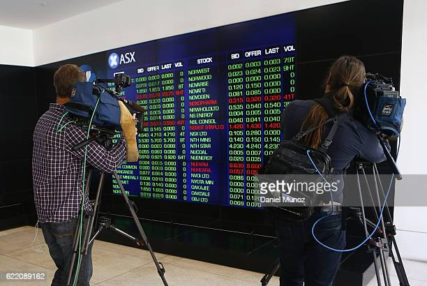 Cameramen work in front of the main board of the Australian Securities Exchange building on November 10 2016 in Sydney Australia Americans voted...