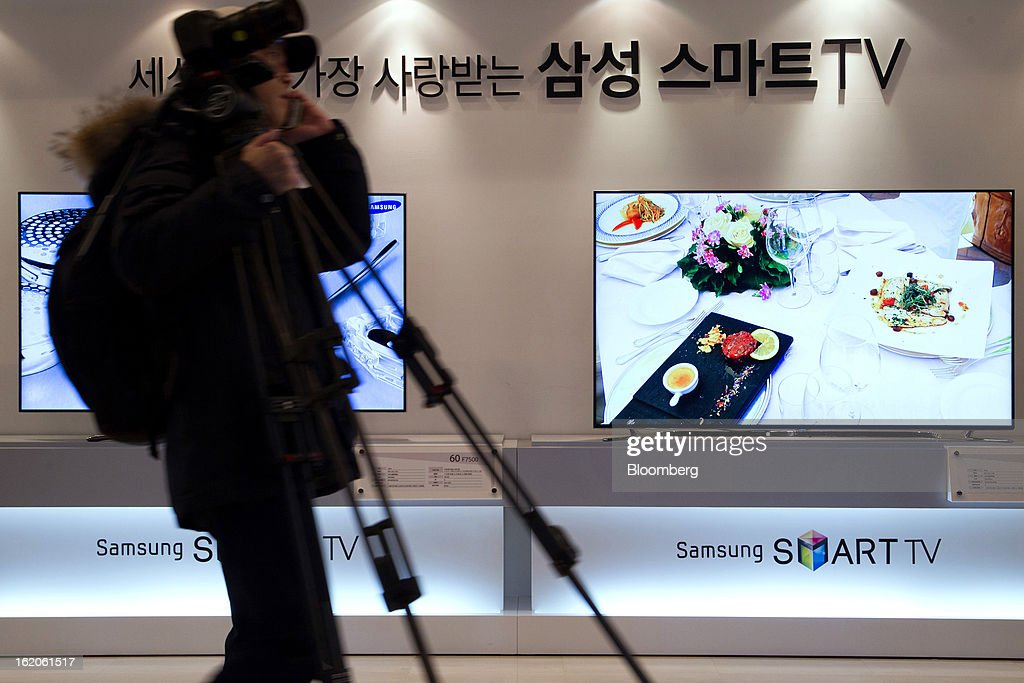 A cameraperson carries equipment past Samsung Electronics Co.'s F8000 series smart televisions as they are displayed at a media event in Seoul, South Korea, on Tuesday, Feb. 19, 2013. Samsung Electronics Co., the world's largest television maker, targets to start selling TVs using a technology allowing brighter and sharper images in the first half to extend its market lead. Photographer: SeongJoon Cho/Bloomberg via Getty Images