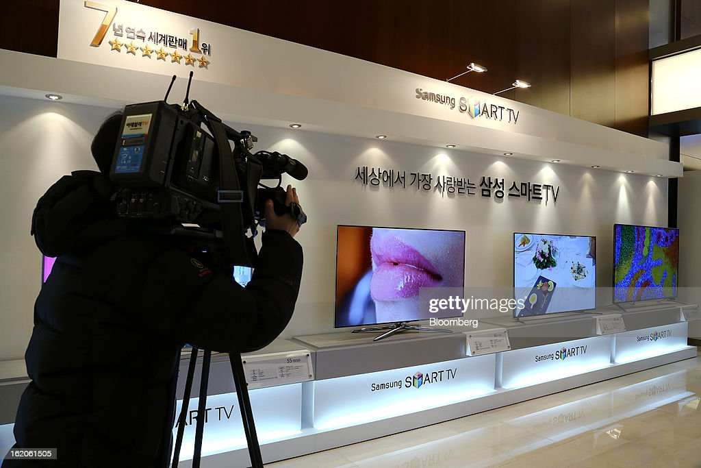 A cameraperson films Samsung Electronics Co.'s F8000 series smart televisions as they are displayed at a media event in Seoul, South Korea, on Tuesday, Feb. 19, 2013. Samsung Electronics Co., the world's largest television maker, targets to start selling TVs using a technology allowing brighter and sharper images in the first half to extend its market lead. Photographer: SeongJoon Cho/Bloomberg via Getty Images