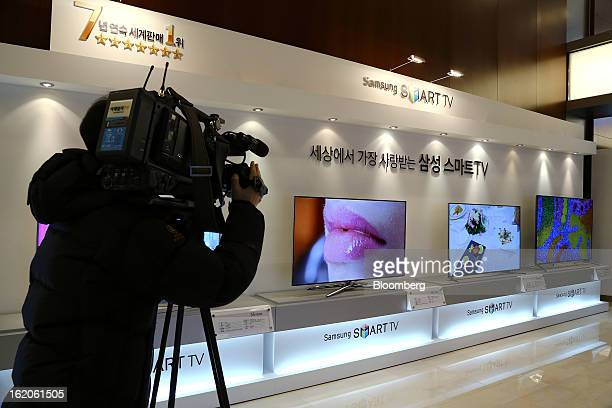 A cameraperson films Samsung Electronics Co's F8000 series smart televisions as they are displayed at a media event in Seoul South Korea on Tuesday...