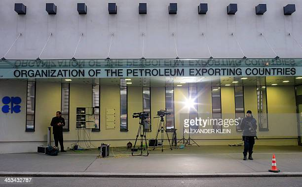 TV cameras and armed police are seen outside the headquarters of OPEC ahead of the164th OPEC meeting in Vienna on December 4 2013 OPEC is set to...