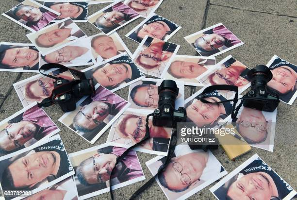 TOPSHOT Cameras and pictures of journalists recently murdered in different Mexican states are placed at Independence Angel square during a protest by...
