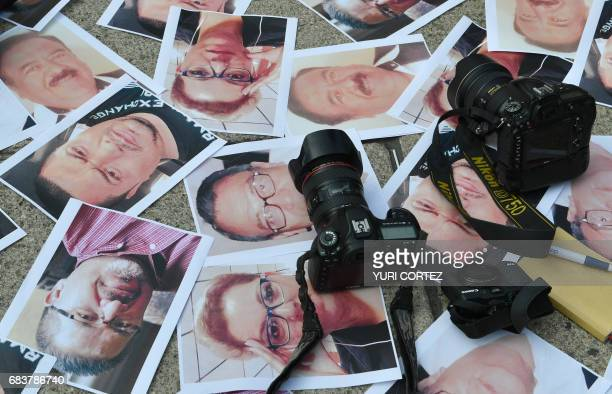 Cameras and pictures of journalists recently murdered in different Mexican states are placed at Independence Angel square during a protest by...