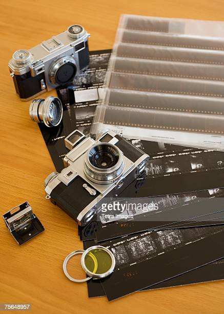 Cameras, negatives and contact sheets on table