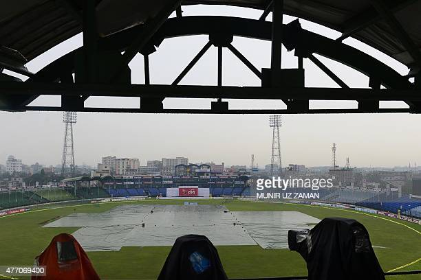 Cameras used to broadcast the match look out over the playing field covered due to rain on the final day of the cricket Test match between Bangladesh...