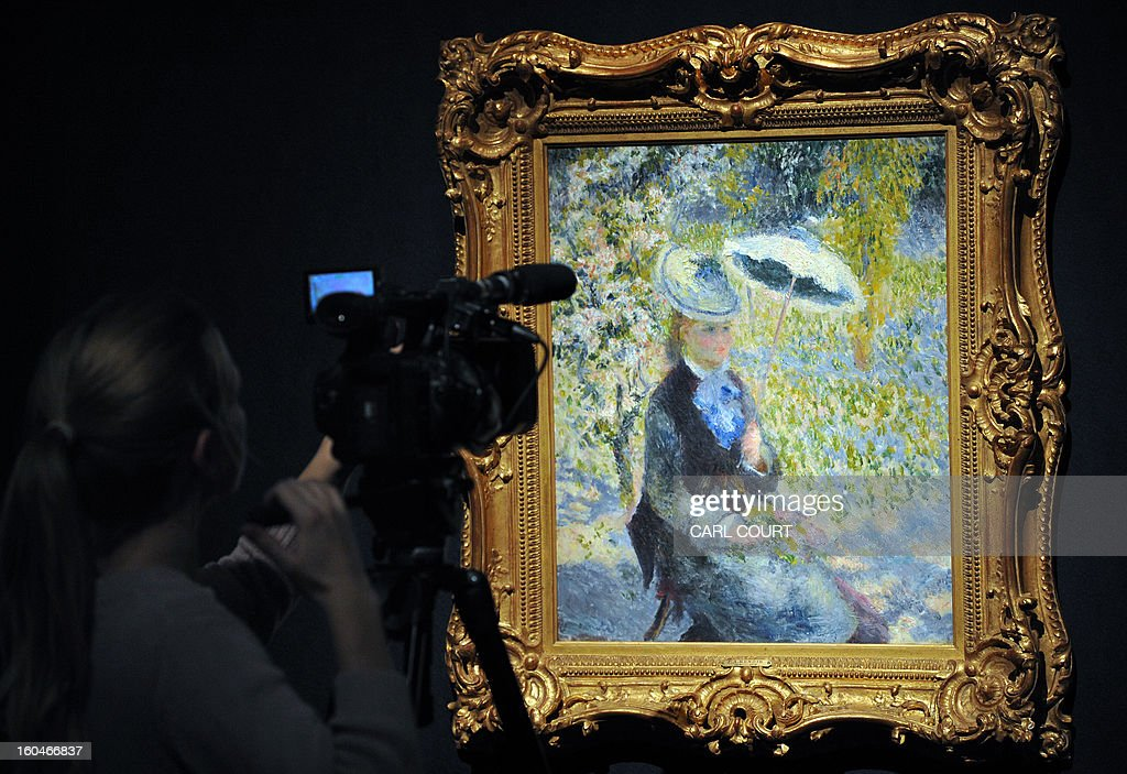 A camerawoman films a work entitled 'L'ombrelle ' by French artist Pierre-Auguste Renoir at Christies auction house in central London on February 1, 2013. Due to form part of the Impressionist and Modern Art Evening Sale on February 6, it is expected to fetch between 4-7 million GBP (6.1-11 million USD - 4.5-7.9 million EUR).