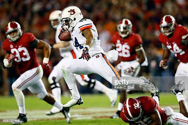 Cameron ArtisPayne of the Auburn Tigers leaps over Rashaan Evans of the Alabama Crimson Tide in the fourth quarter during the Iron Bowl at...