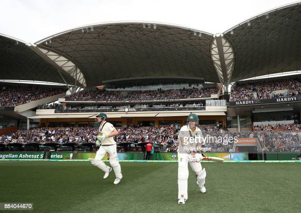 Cameron Bancroft and David Warner of Australia walk out to bat during day one of the Second Test match during the 2017/18 Ashes Series between...