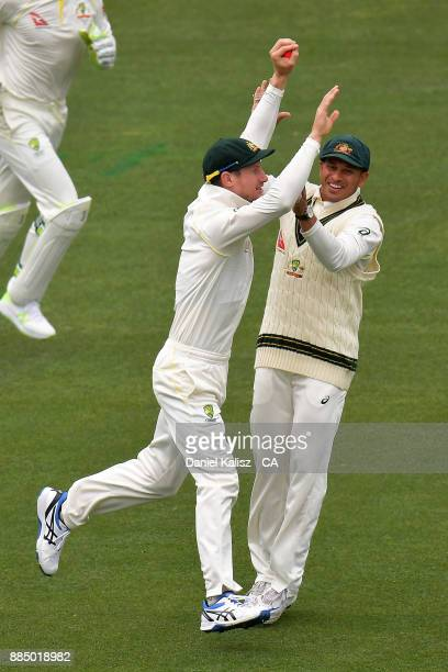 Cameron Bancroft of Australia celebrates with Usman Khawaja of Australiaw after taking a catch to dismiss Joe Root of England during day three of the...