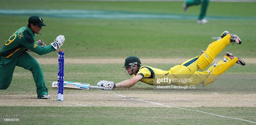 Cameron Bancroft of Australia dives to make his ground as Quinton De Kock (L) of South Africa attempts to run him out during the ICC U19 Cricket World Cup 2012 Semi Final match between Australia and South Africa at Tony Ireland Stadium on August 21, 2012 in Townsville, Australia.