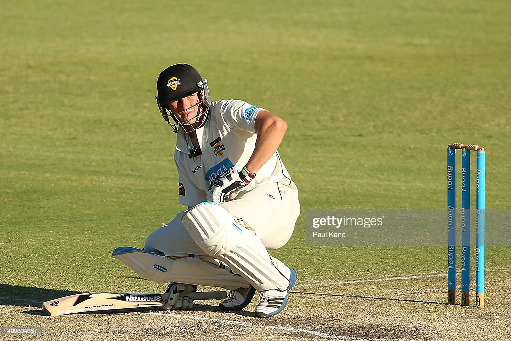 Cameron Bancroft of the Warriors crouches on the pitch after being struck by a delivery during day three of the Sheffield Shield match between the Western Australia Warriors and the Tasmania Tigers at the WACA on February 14, 2014 in Perth, Australia.