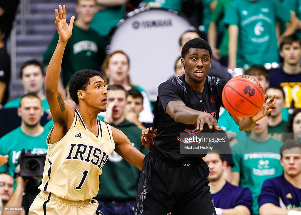 Cameron Biedscheid #1 of the Notre Dame Fighting Irish guards Shaquille Thomas #3 of the Cincinnati Bearcats as he passes the ball off at Purcel Pavilion on February 24, 2013 in South Bend, Indiana. Notre Dame defeated Cincinnati 62-41.