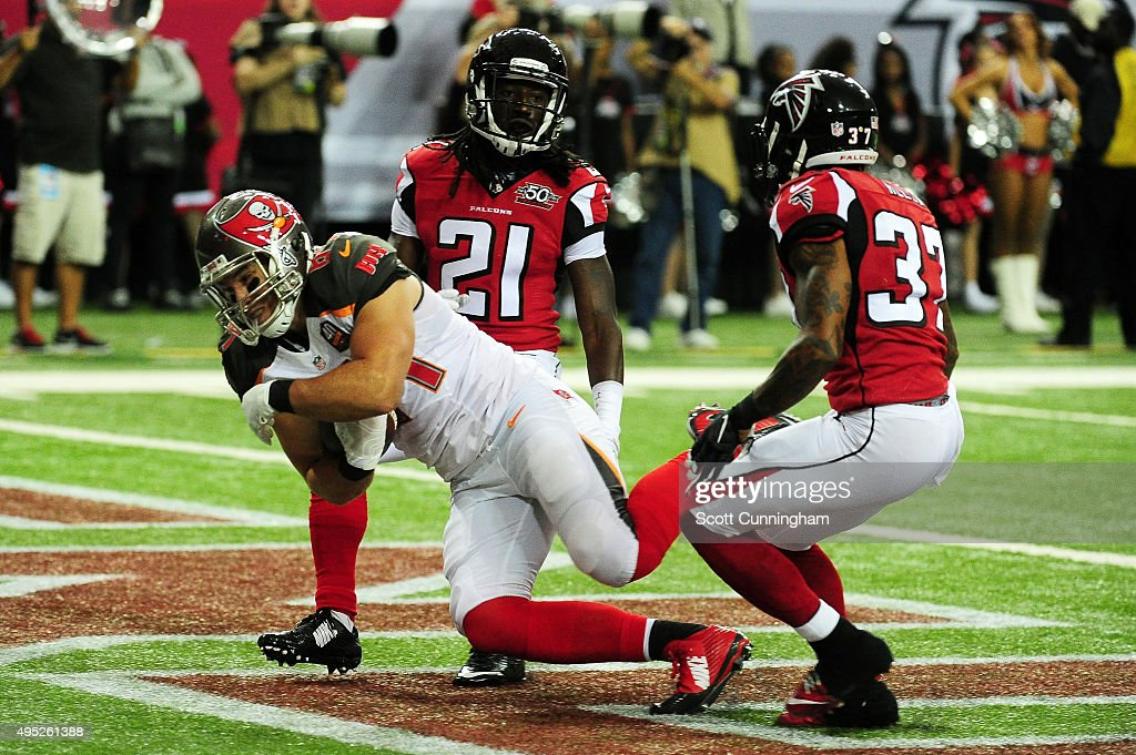 Cameron Brate #84 of the Tampa Bay Buccaneers catches a touchdown pass over Desmond Trufant #21 and Ricardo Allen #37 of the Atlanta Falcons during the first half at the Georgia Dome on November 1, 2015 in Atlanta, Georgia.