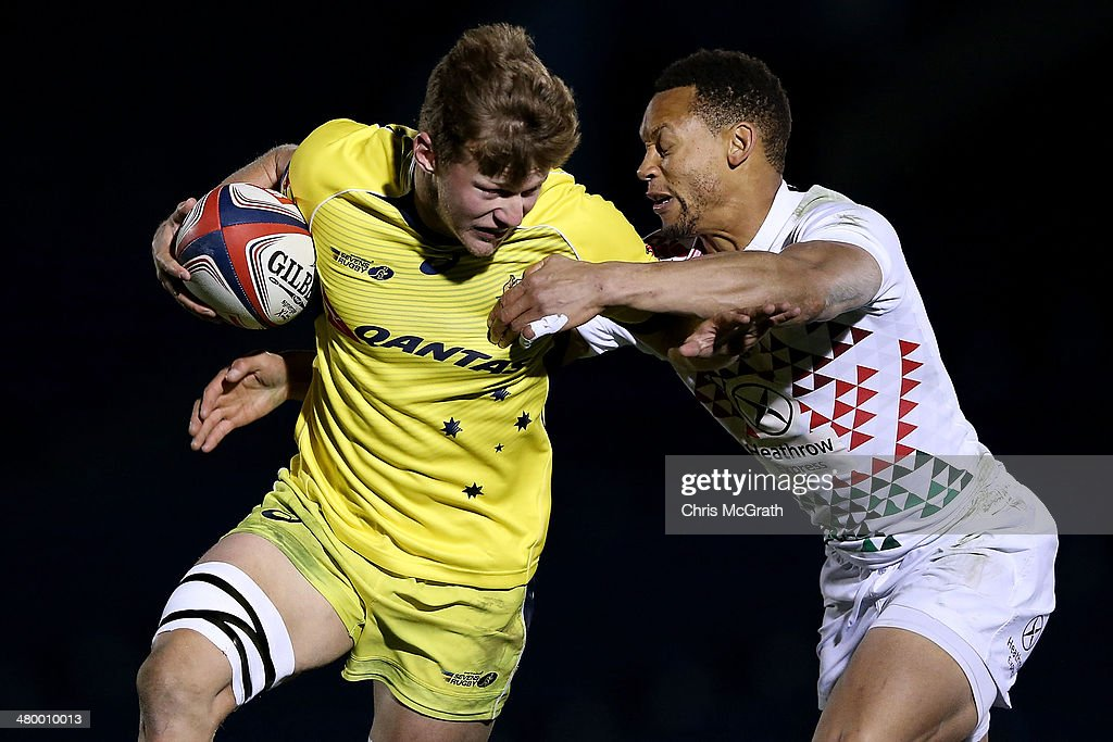 Cameron Clark #7 of Australia fends off Dan Norton #4 of England during the Tokyo Sevens, in the six round of the HSBC Sevens World Series at the Prince Chichibu Memorial Ground on March 22, 2014 in Tokyo, Japan.