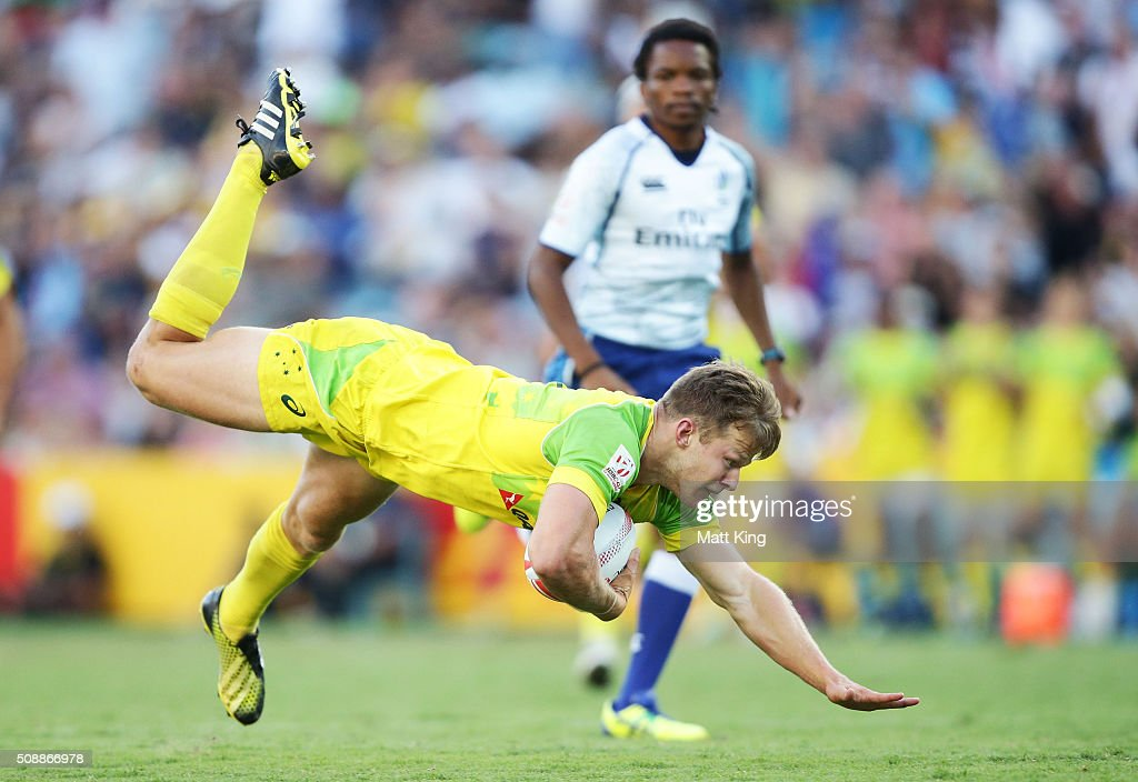 Cameron Clark of Australia trips from an ankle tap from Sonny Bill Williams of New Zealand during the 2016 Sydney Sevens Cup Final match between Australia and New Zealand at Allianz Stadium on February 7, 2016 in Sydney, Australia.