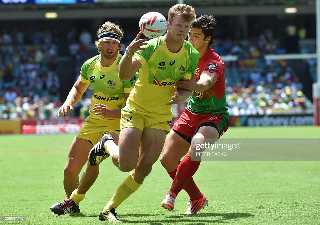Cameron Clarke (C) and Lewis Holland (L) of Australia fight for the ball with Vasco Ribeiro (R) of Portugal in their Pool A match in the Sydney Sevens rugby Union tournament in Sydney on February 6, 2016. AFP PHOTO / Peter PARKS -- IMAGE RESTRICTED TO EDITORIAL USE - NO COMMERCIAL USE / AFP / PETER PARKS