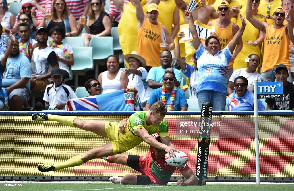 Cameron Clarke of Australia (top) scores a try as he is tackled by Tiago Fernandes of Portugal (bottom) in their Pool A match in the Sydney Sevens rugby Union tournament in Sydney on February 6, 2016. AFP PHOTO / Peter PARKS -- IMAGE RESTRICTED TO EDITORIAL USE - NO COMMERCIAL USE / AFP / PETER PARKS