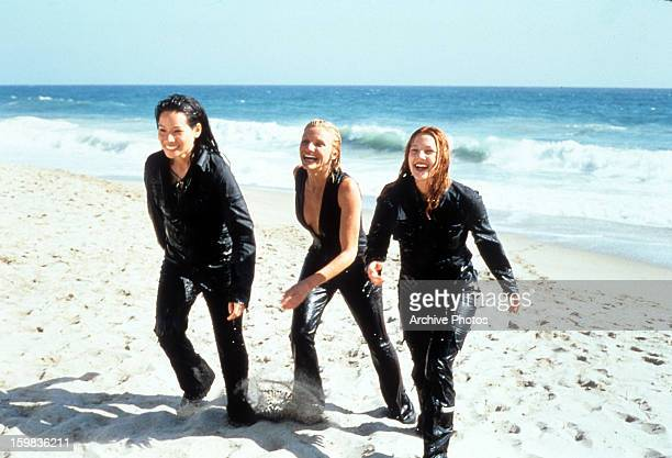 Cameron Diaz Drew Barrymore and Lucy Liu walking up the sand of a beach in a scene from the film 'Charlie's Angels' 2000