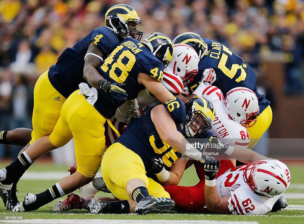 Cameron Gordon #4, Desmond Morgan #48 and AJ Pearson #36 of the Michigan Wolverines help bring down Ameer Abdullah #8 of the Nebraska Cornhuskers in the first quarter at Michigan Stadium on November 9, 2013 in Ann Arbor, Michigan.
