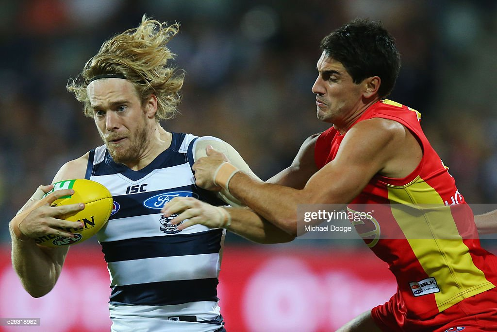 Cameron Guthrie of the Cats is tackled by Matt Rosa of the Suns during the round six AFL match between the Geelong Cats and the Gold Coast Suns at Simonds Stadium on April 30, 2016 in Geelong, Australia.