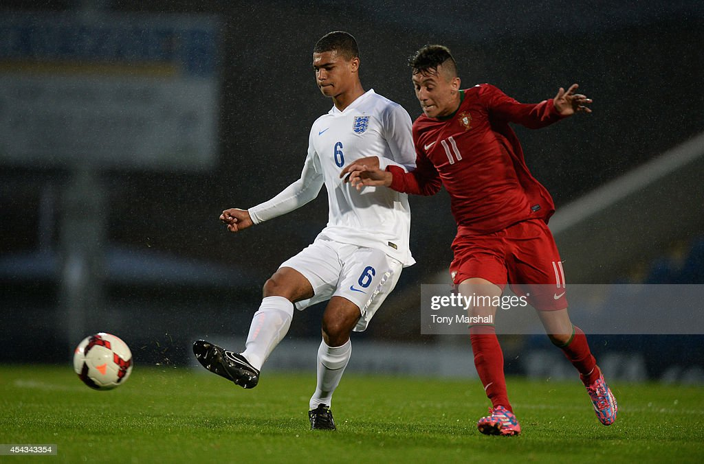 Cameron Humphreys of England is tackled by Tiago Dias of Portugal during the Under 17 International match between England U17 and Portugal U17 at Proact Stadium on August 29, 2014 in Chesterfield, England.