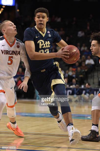 Cameron Johnson of the Pittsburgh Panthers drives against Kyle Guy of the Virginia Cavaliers during the second round of the ACC Basketball Tournament...