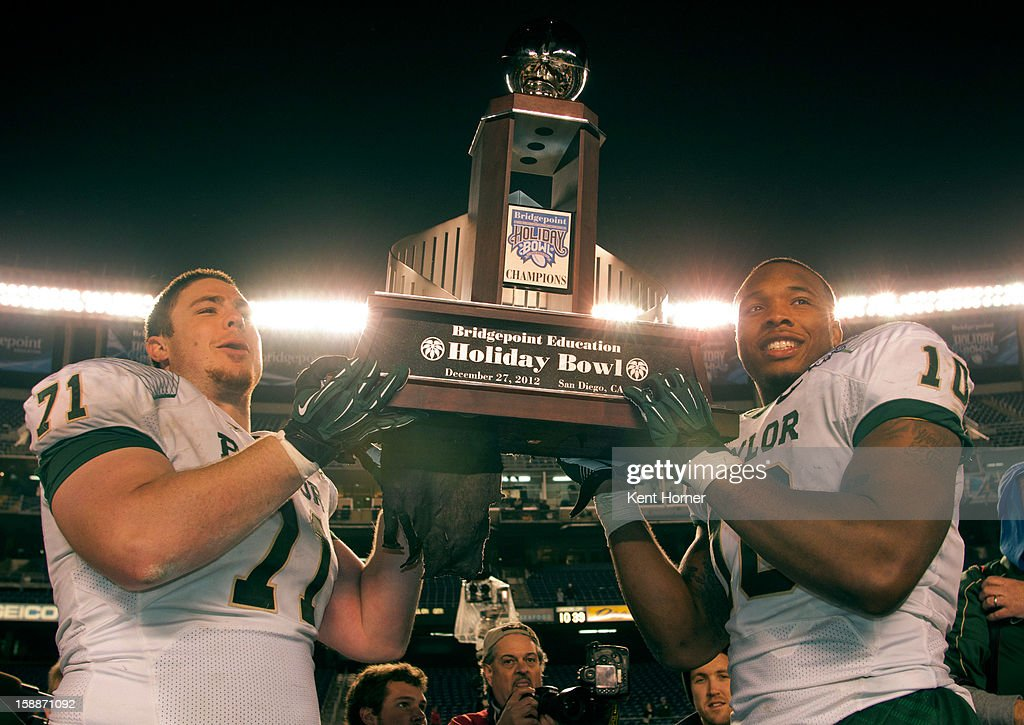 SAN DIEGO, CA - DECEMBER 27 - Cameron Kaufhold #71 and Gary Mason #10 of the Baylor Bears hoist the champion's trophy after beating the UCLA Bruins 49-26 in the Bridgepoint Education Holiday Bowl at Qualcomm Stadium on December 27, 2012 in San Diego, California.