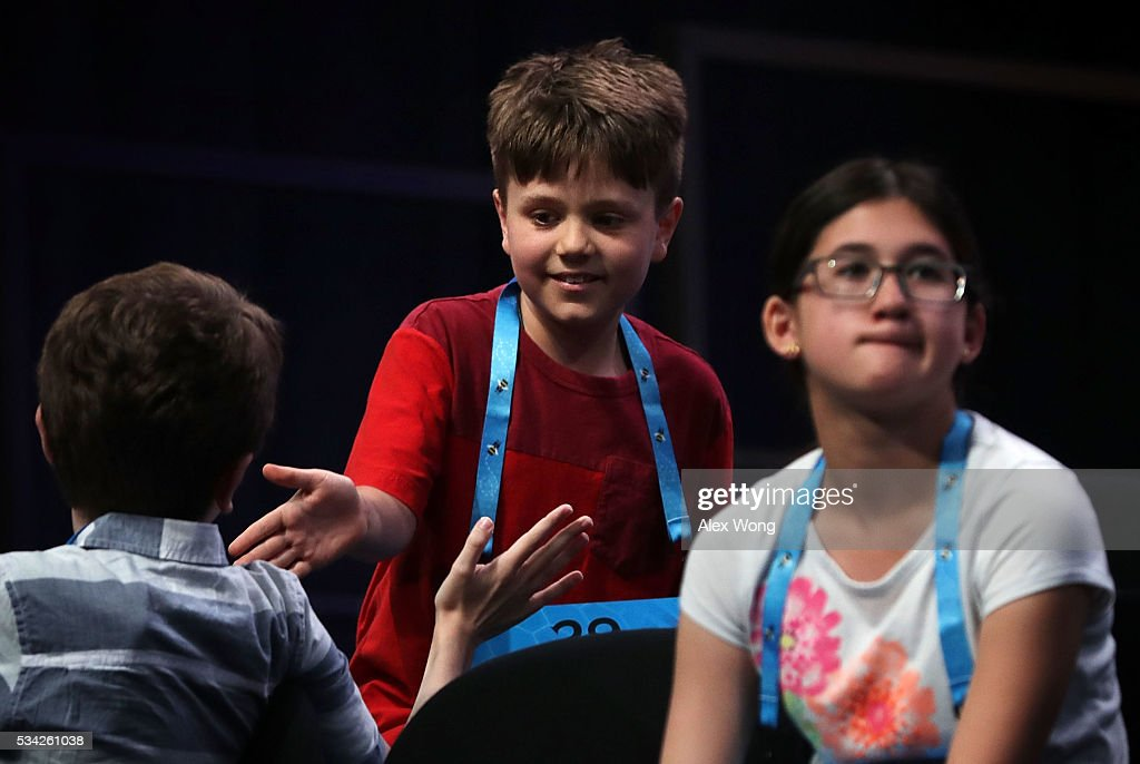 Cameron Keith (C) of Longmont, Colorado, celebrates with another speller after he correctly spelled his word in round three of the 2016 Scripps National Spelling Bee May 25, 2016 in National Harbor, Maryland. Students from across the country gathered to compete for top honor of the annual spelling championship.