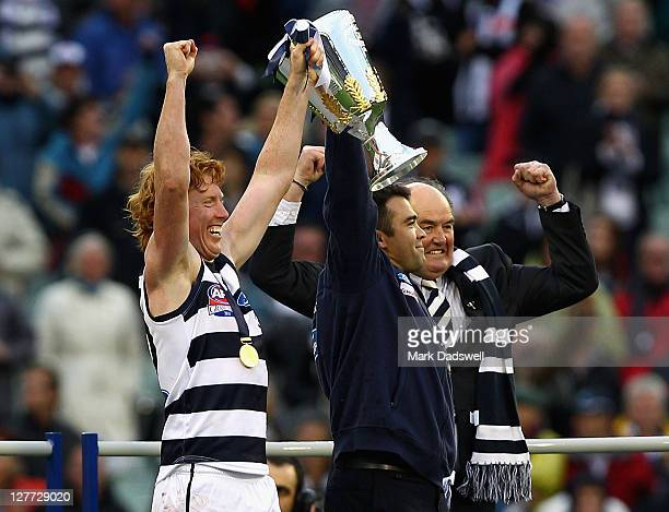 Cameron Ling captain and Chris Scott coach of the Geelong Football Club receive the premiership cup from club legend Doug Wade after winning the 2011...