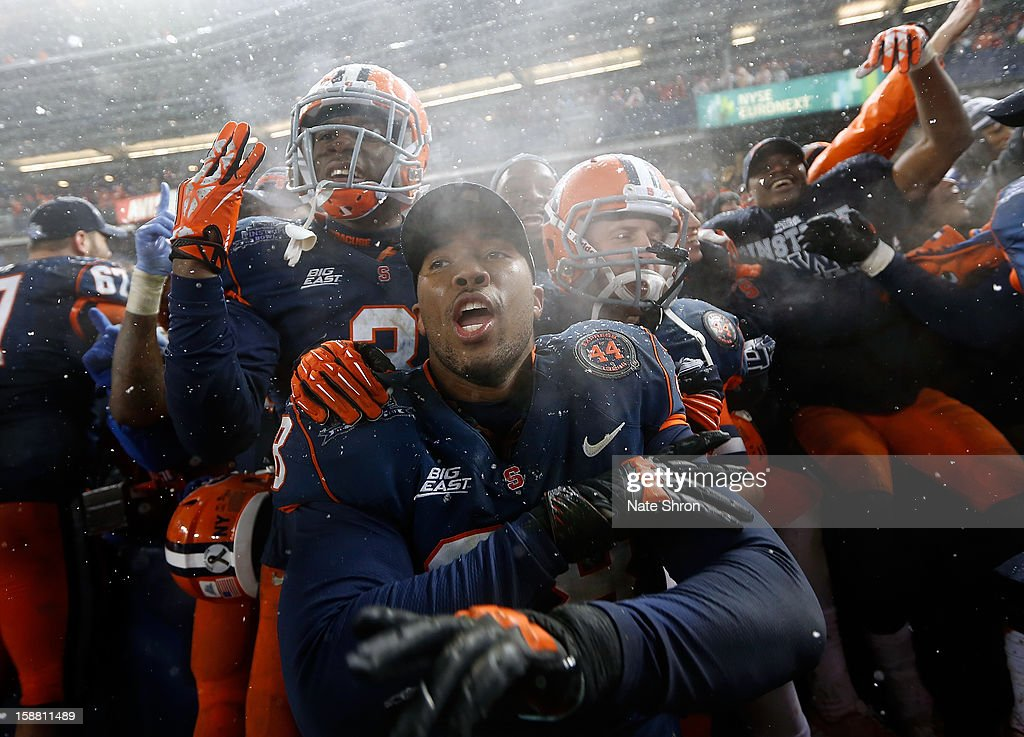 Cameron Lynch #38 (Center) of the Syracuse Orange celebrates with teamates after the win over the West Virginia Mountaineers during the New Era Pinstripe Bowl at Yankee Stadium on December 29, 2012 in the Bronx borough of New York City.