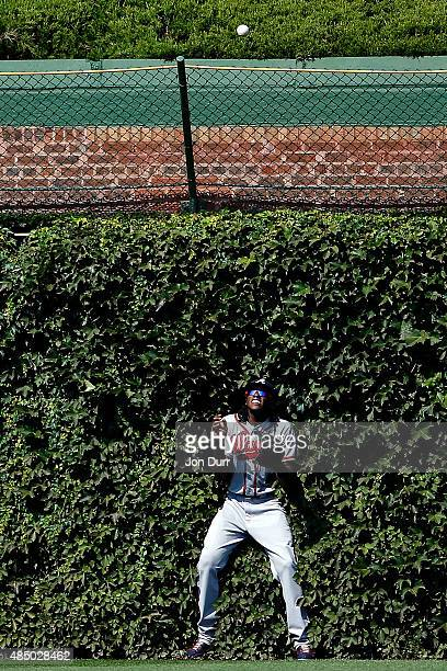 Cameron Maybin of the Atlanta Braves looks at the homerun ball of Kris Bryant of the Chicago Cubs during the sixth inning at Wrigley Field on August...