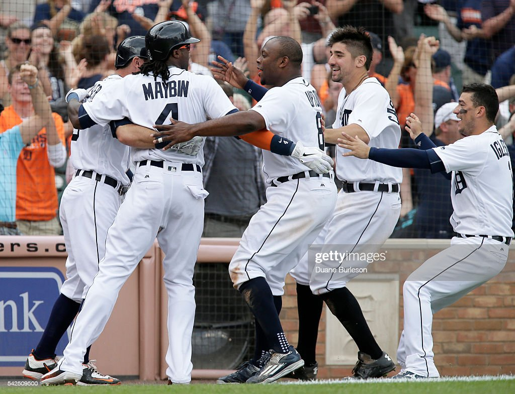 <a gi-track='captionPersonalityLinkClicked' href=/galleries/search?phrase=Cameron+Maybin&family=editorial&specificpeople=2364846 ng-click='$event.stopPropagation()'>Cameron Maybin</a> #4 of the Detroit Tigers is surrounded by <a gi-track='captionPersonalityLinkClicked' href=/galleries/search?phrase=Ian+Kinsler&family=editorial&specificpeople=538104 ng-click='$event.stopPropagation()'>Ian Kinsler</a> #3, <a gi-track='captionPersonalityLinkClicked' href=/galleries/search?phrase=Justin+Upton&family=editorial&specificpeople=846265 ng-click='$event.stopPropagation()'>Justin Upton</a> #8, <a gi-track='captionPersonalityLinkClicked' href=/galleries/search?phrase=Nick+Castellanos&family=editorial&specificpeople=6129175 ng-click='$event.stopPropagation()'>Nick Castellanos</a> #9, and Jose Iglesias #1 of the Detroit Tigers after scoring from third base on a wild pitch by Steve Cishek #31 of the Seattle Mariners to win the game 5-4 in 10 innings at Comerica Park on June 23, 2016 in Detroit, Michigan. Maybin was pinch running for Steven Moya of the Detroit Tigers.