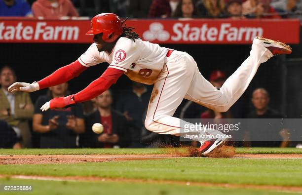 Cameron Maybin of the Los Angeles Angels is safe at home as he beats the tag by Russell Martin of the Toronto Blue Jays in the fifth inning of the...