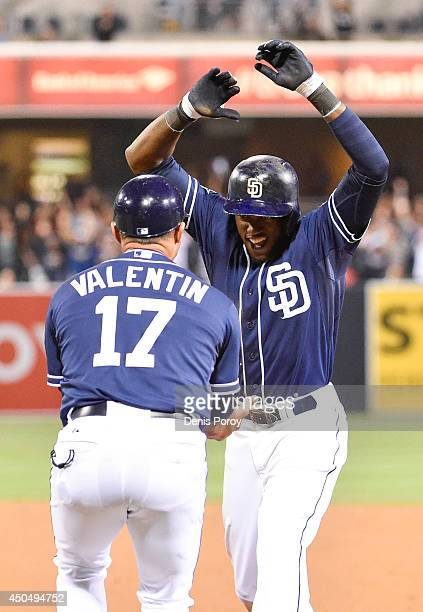 Cameron Maybin of the San Diego Padres celebrates his walkoff single with Jose Valentin during the eleventh inning of a baseball game against the...
