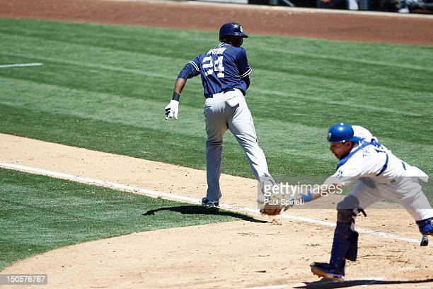 Cameron Maybin of the San Diego Padres looks back at Matt Treanor of the Los Angeles Dodgers who catches a bunt popup for an out during the game on...