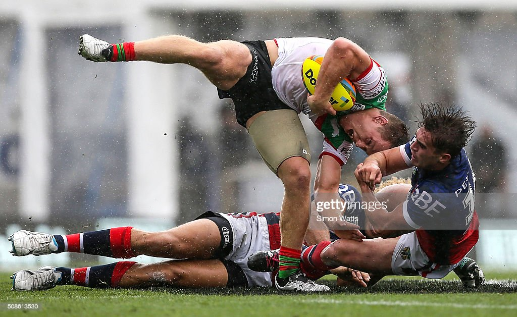 Cameron Mcinnes of the Rabbitohs is tackled by Connor Watson (R) and Brendan Elliot of the Roosters during the 2016 Auckland Nines match between the Sydney Roosters and the South Sydney Rabbitohs at Eden Park on February 6, 2016 in Auckland, New Zealand.