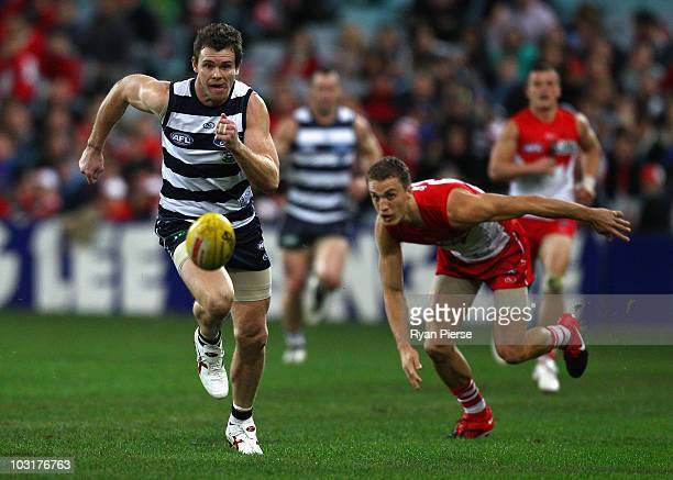 Cameron Mooney of the Cats chases the ball ahead of Ted Richards of the Swans during the round 18 AFL match between the Sydney Swans and the Geelong...