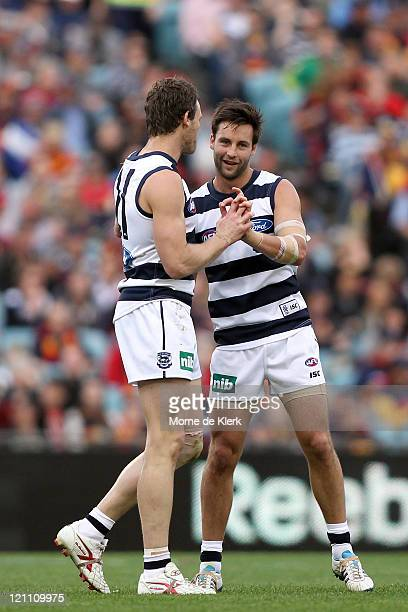 Cameron Mooney of the Cats congratulates team mate Jimmy Bartel after Bartel kicked a goal during the round 21 AFL match between the Adelaide Crows...