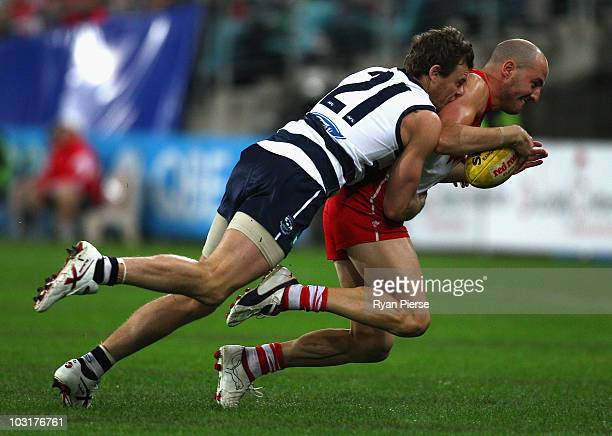 Cameron Mooney of the Cats tackles Tadhg Kennelly of the Swans during the round 18 AFL match between the Sydney Swans and the Geelong Cats at ANZ...
