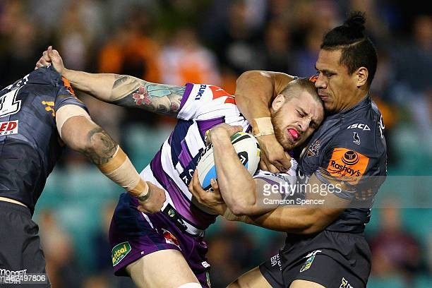 Cameron Munster of the Storm is tackled during the round 21 NRL match between the Wests Tigers and the Melbourne Storm at Leichhardt Oval on July 31...