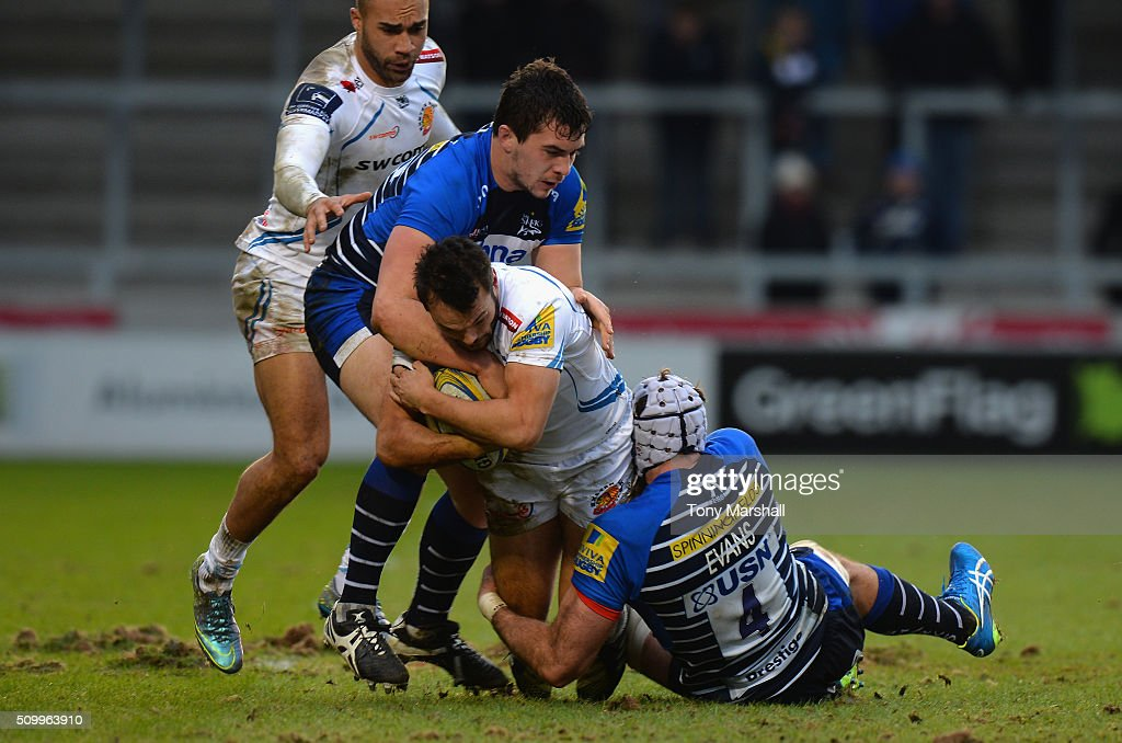 Cameron Neild and Bryn Evans of Sale Sharks tackle Phil Dollman of Exeter Chiefs during the Aviva Premiership match between Sale Sharks and Exeter Chiefs at the A J Bell Stadium on February 13, 2016 in Salford, England