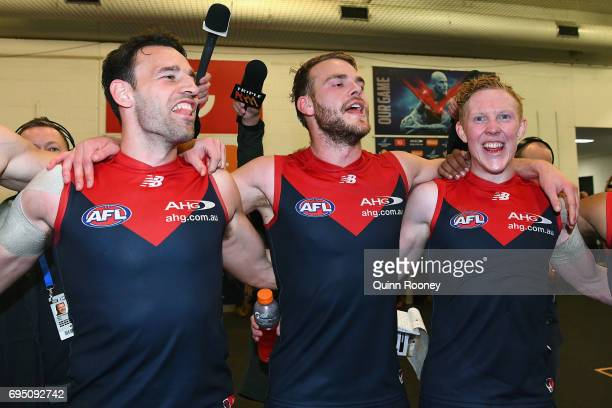 Cameron Pedersen Jack Watts and Clayton Oliver of the Demons sing the song in the rooms after winning the round 12 AFL match between the Melbourne...