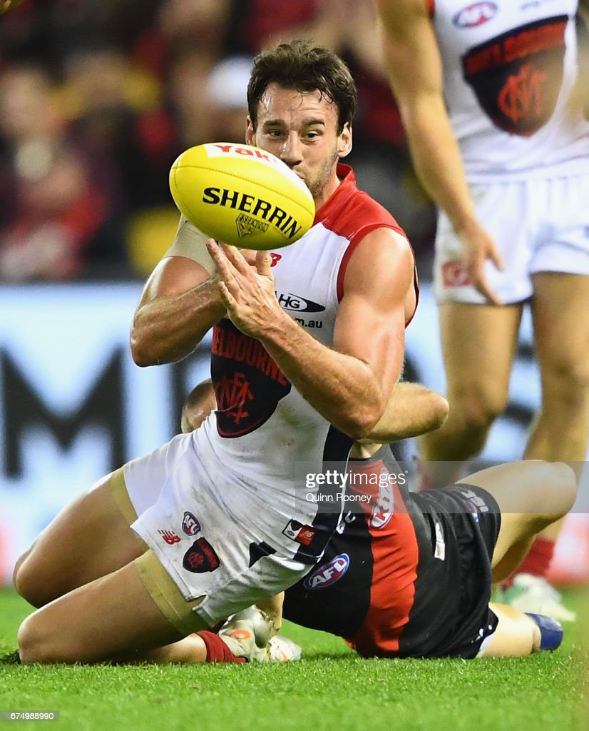 Cameron Pedersen of the Demons handballs whilst being tackled during the round six AFL match between the Essendon Bombers and the Melbourne Demons at Etihad Stadium on April 30, 2017 in Melbourne, Australia.