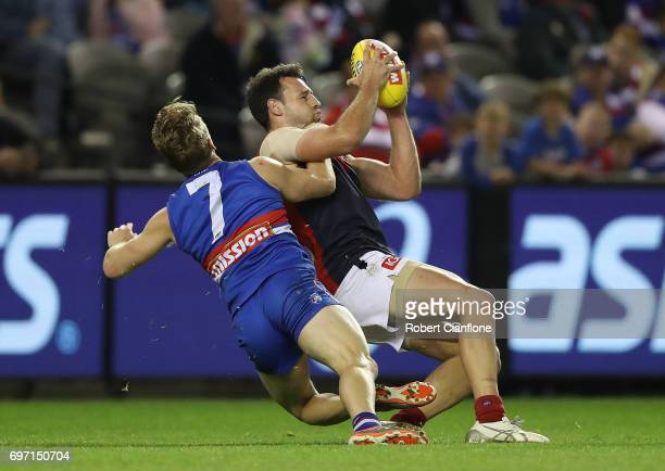 Cameron Pedersen of the Demons marks in front of Lachie Hunter of the Bulldogs during the round 13 AFL match between the Western Bulldogs and the...