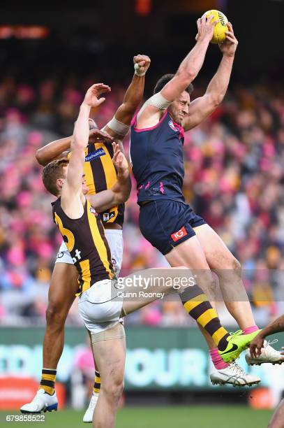 Cameron Pedersen of the Demons marks infront of Josh Gibson of the Hawks during the round seven AFL match between the Melbourne Demons and the...