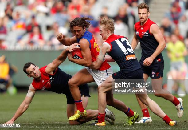 Cameron Pedersen of the Demons Rhys Mathieson of the Lions and Clayton Oliver of the Demons compete for the ball during the 2017 AFL round 22 match...