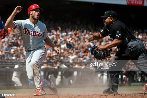 Cameron Perkins of the Philadelphia Phillies reacts after getting called out by umpire Adrian Johnson on a tag at home plate by Buster Posey of the...